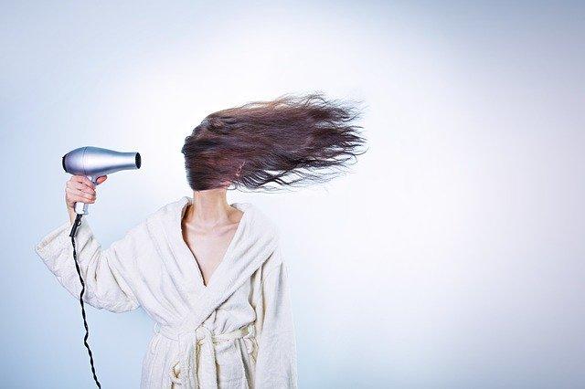 žena fénující si vlasy